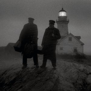 Ephraim (Robert Pattinson) och Thomas (Willem Dafoe) står i regn och blåst på klippor, i bakgrunden syns fyren.