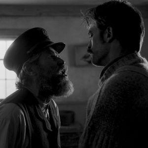 Thomas (Willem Dafoe) och Ephraim (Robert Pattinson) står mittemot varandra och ser arga ut.