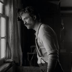 Ephraim (Robert Pattinson) står vid ett fönster och ser ut.