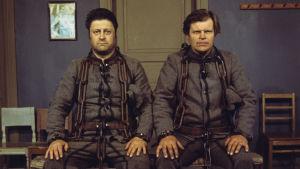 Harri Tirkkonen ja Kalevi Haapoja esittävät Antti Rannanjärveä ja Antti Isotaloa tv-elokuvassa Häjyt. Kuvassa istuvat pidätettyinä, paksut ketjut kaulassa.
