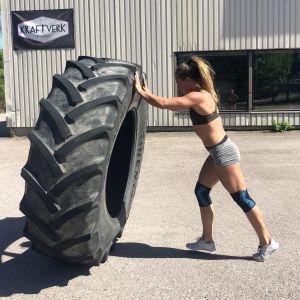 Sara Pihlflyckt knuffar ett traktorhjul.