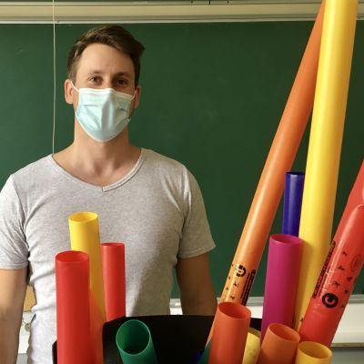 Man med munskydd  står framför svarta tavlan i klassrum, framför sig har han färgglada plaströr.