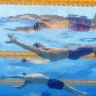 Tre ryggsimmare bredvid varandra i bassängen under tävling.