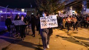 """""""Walter hade också en familj"""" står det på den här demonstrantens plakat, med hänvisning till 27-åringen som sköts ihjäl av poliser i Philadelphia."""