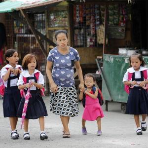 En filippinsk mamma tar sina barn till skolan i huvudstaden Manila.