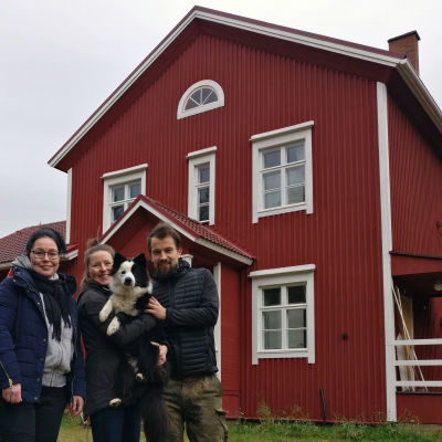 Maria Jyrkäs, Vilma Pellinen sekä Janne Uusitalo kaksikerroksisen puutalon edustalla. Vilma ja Janne pitelevät yhdessä mustavalkoista koiraa sylissään.