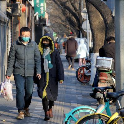En man och en kvinna iförda ansiktsmasker promenerar längs en gata i Peking