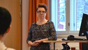 Sofia Mitts-Björkblom står och  lutar sig mot ett databord.