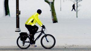 En man iklädd en neongul cykeljacka, cyklar på en snötäckt väg. I bakgrunden syns en snöklädd park och en man som går.