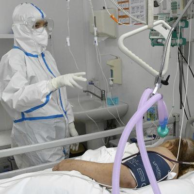 En sjukskötare i skyddsutrustning står vid en sjukhussäng där en coronapatient ligger.