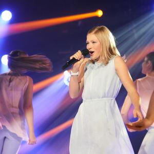 Milou i vit klänning tillsammans med dansare.