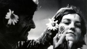 En hippieman målar en blomma på en hippikvinnas kind