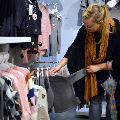 Nina Nyman i en klädbutik där hon håller en tröja i handen.