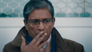 En rökande pappa Mirza i närbild.