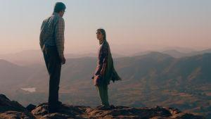 Far och dotter stående vid kanten av ett högt berg.