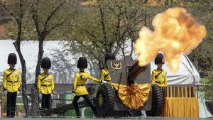 Thailändska kungliga vakter avfyrar artilleri för att hylla kungen utanför palatset i Bangkok.