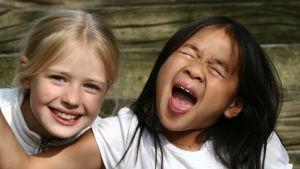 Två flickor som sitter bredvid varandra. Den ena tittar nyfiket in i kameran, den andra blundar och ropar något.