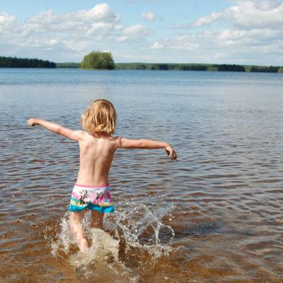 Ett barn springer i vattenbrynet.