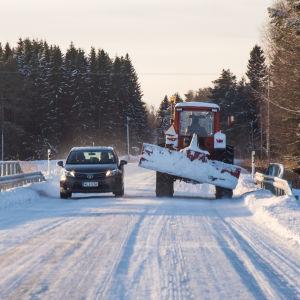 En personbil och en traktor med schaktblad möts på en isbelagd väg.
