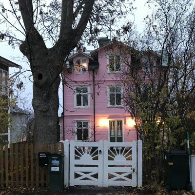 Rosa trähus i tre våningar med vita portar.