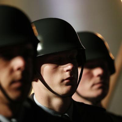 Närbild på tre uppradade tyska soldater med hjälmar på huvudet vid en festhögtid.