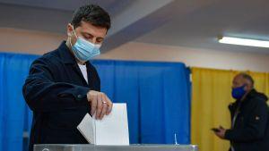 En man (ukrainas president) lägger ner sin röstsedel.