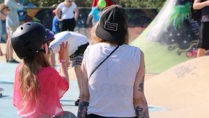 En liten flicka dricker vatten ur en vattenflaska. Hon har en svart hjälm på huvudet och sitter i en rullbrädspark.
