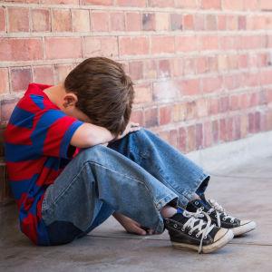 Ett barn ser ut att vara ledsen och sitter i en korridor och täcker sitt ansikte med armarna.