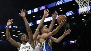 Stephen Curry tar sig förbi Brooklynförsvaret.