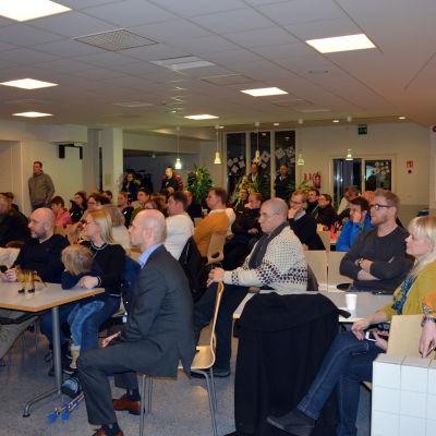 Många människor som  sitter i en skolmatsal och lyssnar på ett möte.