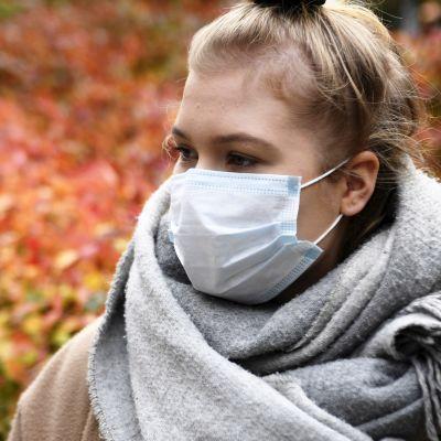 Kvinna står med ett munskydd på sig framför buskar i höstiga färger. Hon har en stor grå halsduk runt halsen.