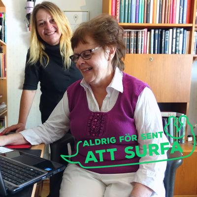 """En äldre kvinna sitter framför en bärbar dator. Bakom henne står en kvinna i medelåldern som ler och ser in i kameran. På bilden finns också en logga med texten """"Aldrig för sent att surfa""""."""