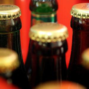 Närbild på bruna glasölflaskor med mässingsfärgade kapsyler.