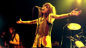 Patti Smith uppträder år 1978. Hon sjunger vid mikrofonen med armarna usträckta åt sidorna.