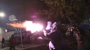 En polis avfyrar tårgas