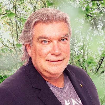Mikael Lindfelt småler in i kameran framför en grönskande bakgrund.