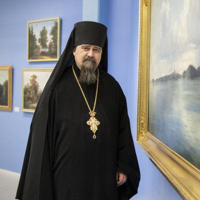 Arkkimandriitta Sergei Valamon luostarin taidenäyttelyssä Ivan Siskinin maisemamaalauksen äärellä.