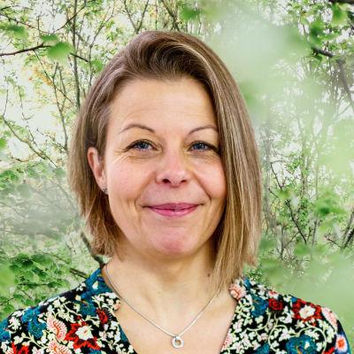 Anette Rönnlund-Nygård småler in i kameran framför en grönskande bakgrund.