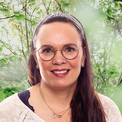 Anna Kolster-Weckström småler in i kameran framför en grönskande bakgrund.