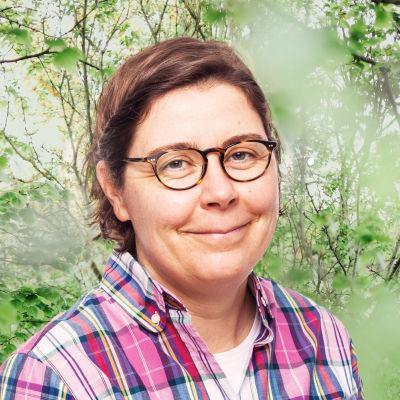 Bigo Lindholm småler in i kameran framför en grönskande bakgrund.