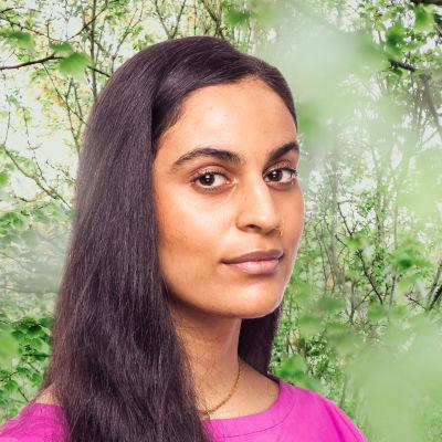 Nayab Ikram småler in i kameran framför en grönskande bakgrund.