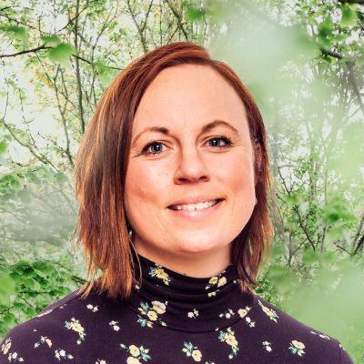 Anna Bertills småler in i kameran framför en grönskande bakgrund.