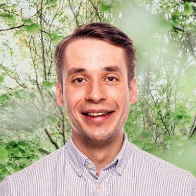 Henrik Wickström ler in i kameran framför en grönskande bakgrund.