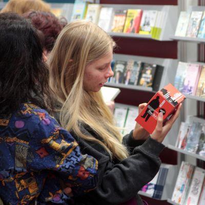 Unga är också intresserade av ljudböcker. Två ungdomar granskar en ljudbok i butikshyllan.