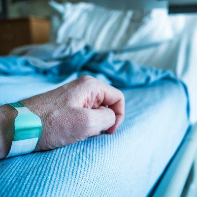 Närbild på en mans arm i en sjukhussäng.