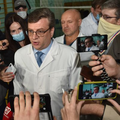 Chefsläkaren Alexander Murachovskij omgiven av journalister den 21.8 då Navalnyj ännu vårdades i Omsk.