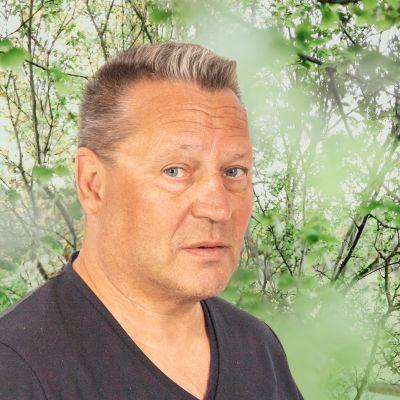 Paul Murphy ser rakt in i kameran. Bakgrunden är en grönskande skogsdunge.