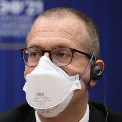 En man i glasögon och munskydd tittar åt sidan. Han är fotograferad framför en blå vägg och har en öronsnäcka i örat.