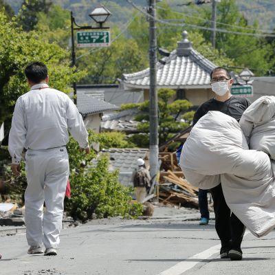 Japanilainen kantaa tavaroita ulkona.