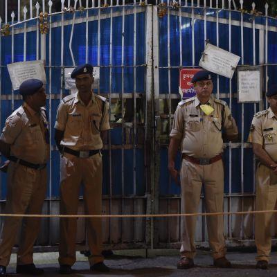 Fem vakter utanför ett stängsel i New Delhi, Indien.